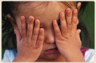 Child hiding face with hands
